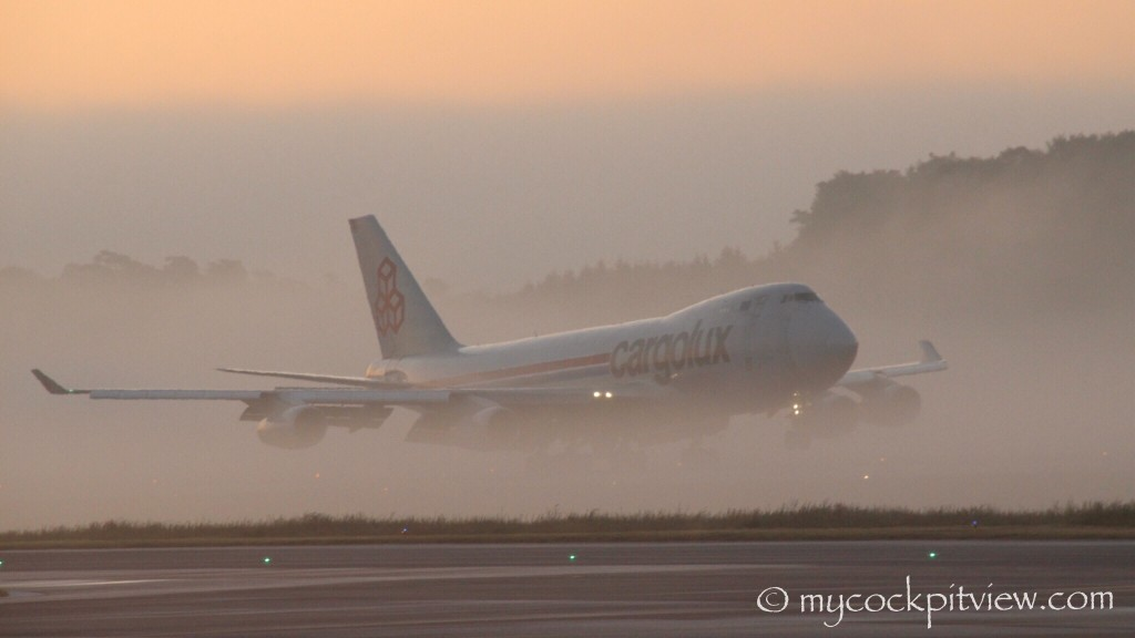Cargolux Boeing 747 Landing on a spring morning in Luxembourg. Fog patches on the runway make it disappear shortly after touch down, leaving only his tail visible. The shark of the sky!