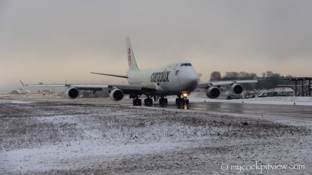 ELLX. LUX. Cargolux Boeing 747-400 taxiing runway 24 in Luxembourg, after a deicingfluid  shower.